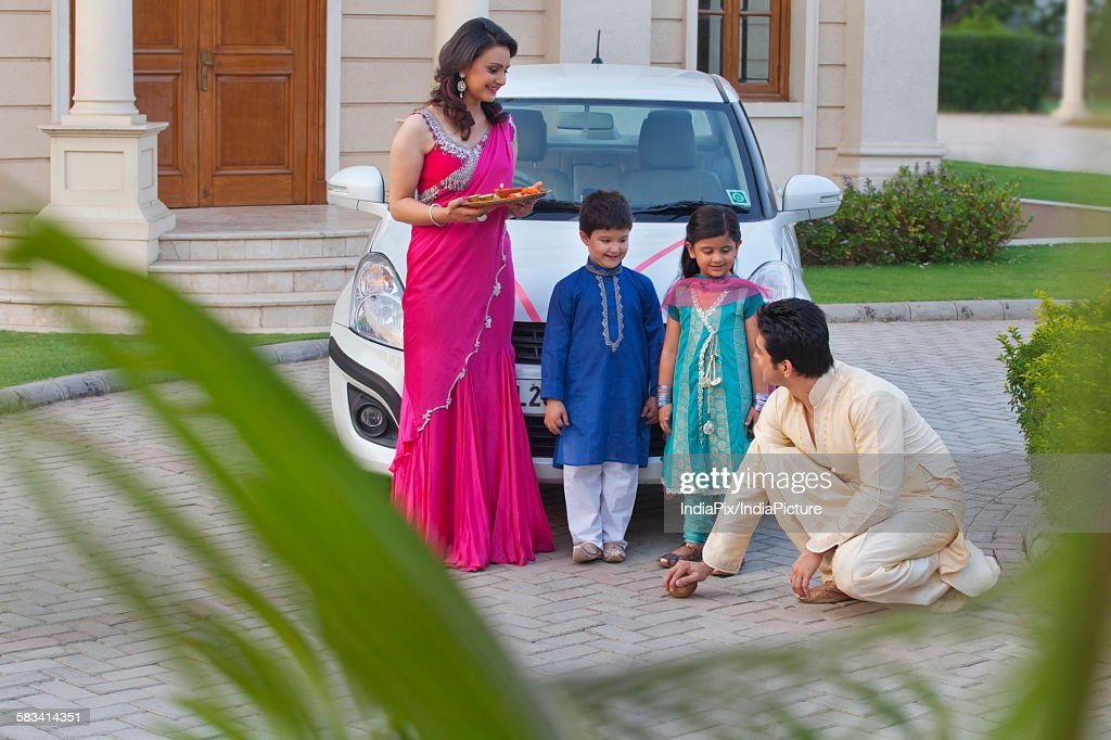 Man breaking coconut on ground as family watches on : Stock Photo