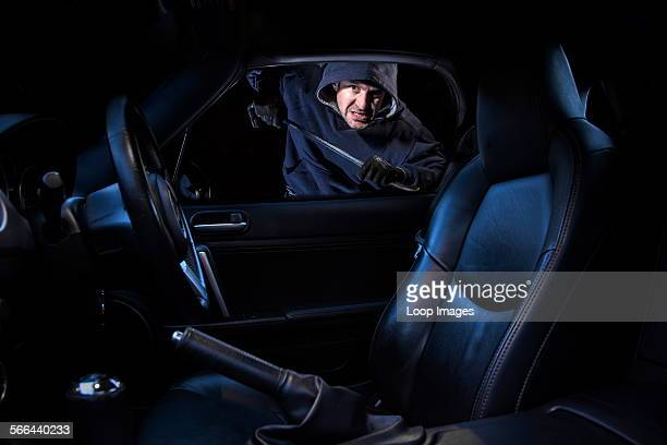 A man breaking into a parked car at night