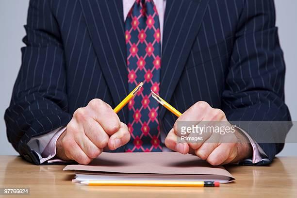 Man breaking pencil