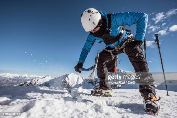 man breaking snow against sky - andrea rizzi stockfoto's en -beelden