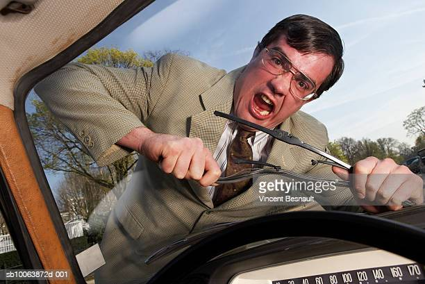Man breaking windshield wiper and yelling, view from car, portrait
