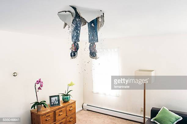 man breaks ceiling drywall while doing diy - practical joke stock photos and pictures