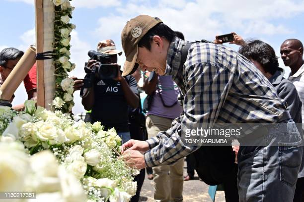 A man breaks down as he lights incense with his family at the crash site of the Ethiopian Airlines operated Boeing 737 MAX aircraft at Hama...