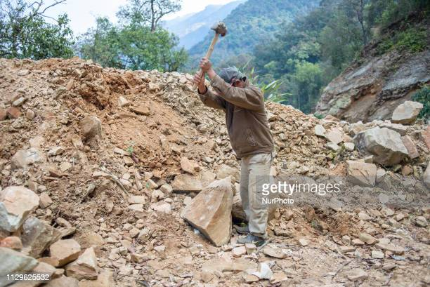 A man breaks stones on a mountain road near Pokhara Nepal in March 2019