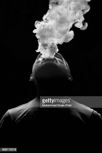 man breathing out smoke