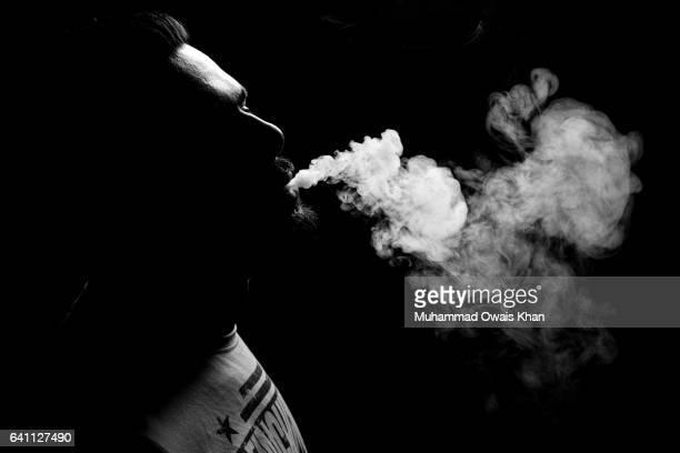 man breathing out smoke