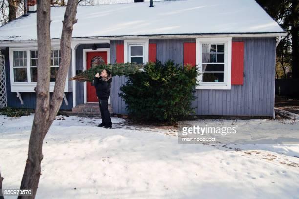 Mann nach Hause zu bringen, den gewählten frischen Weihnachtsbaum im Freien.