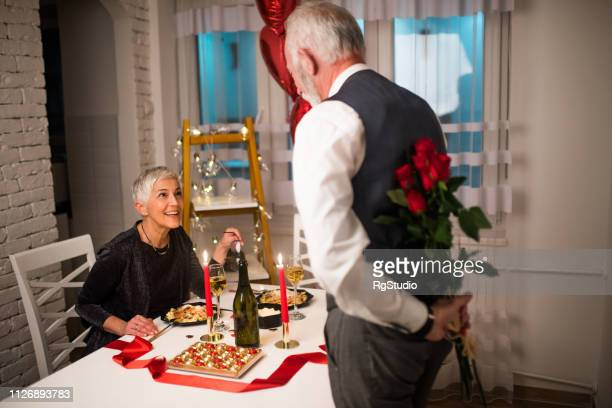 man bringing roses to his wife - valentines day dinner stock pictures, royalty-free photos & images