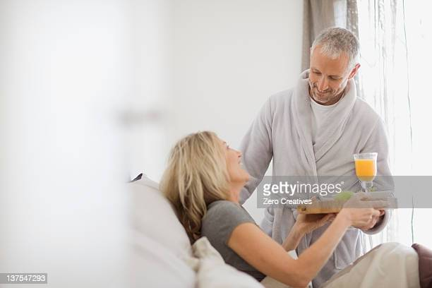 man bringing wife breakfast in bed - breakfast in bed stock pictures, royalty-free photos & images