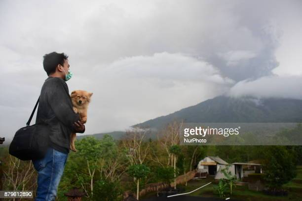 A man brings a dog to see the eruption of Mount Agung which released thick gray smoke and ash with a height up to 3km during an eruption seen from...