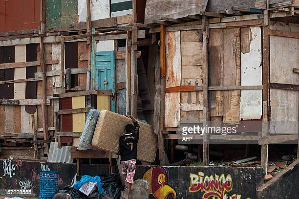 A man brings back mattresses into his home just below the scene of a fire at Paraisopolis shantytown in Sao Paulo Brazil on November 30 2012...