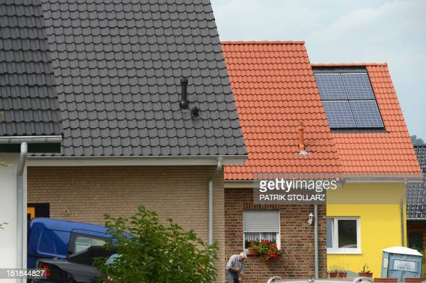 A man brooms in front of a house with solar panels on the roof in Grevenbroich near Aachen western Germany on September 11 2012 AFP PHOTO / PATRIK...