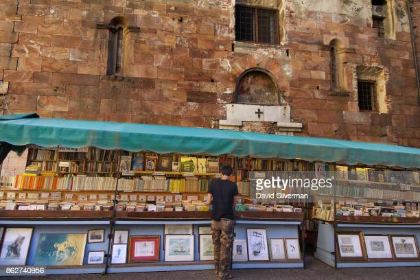 A man browses a secondhand book and map stall near Piazza San Michele on July 24 2015 in Lucca a city in the region of Tuscany Italy Tuscany is...