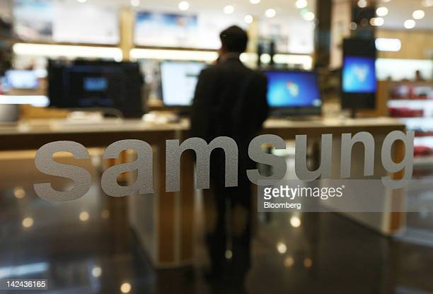 A man browses computer screens behind the Samsung Electronics Co logo at one of the company's offices in Seoul South Korea on Thursday April 5 2012...