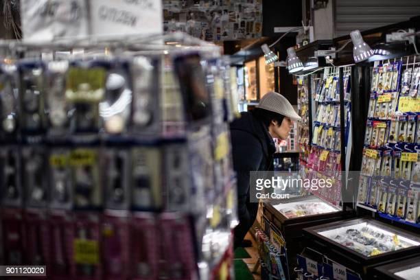 A man browses discount watches on sale in Ameya Yokocho market on January 4 2018 in Tokyo Japan Ameya Yokocho claimed to be Tokyo's last remaining...