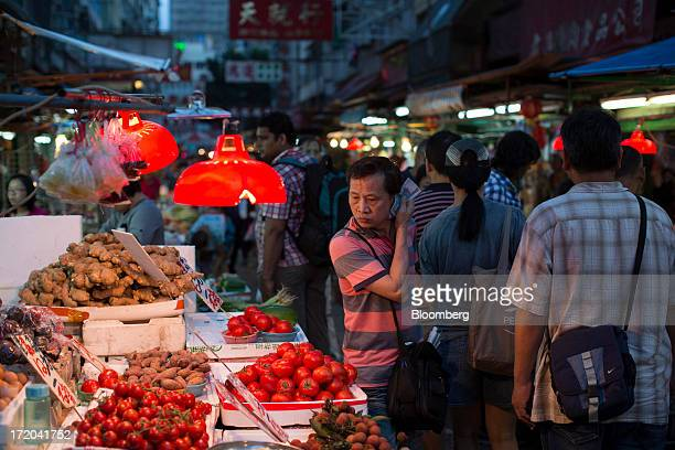 A man browses produce at a stall in a market in the Yau Ma Tei district of Hong Kong China on Saturday June 29 2013Hong Kongs bestselling newspapers...