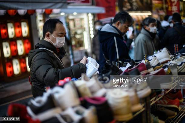 A man browses shoes at a shop in Ameya Yokocho market on January 4 2018 in Tokyo Japan Ameya Yokocho claimed to be Tokyo's last remaining open air...