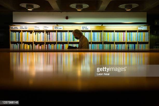Man browses some of the books available in the main area of the Barbican Library following it's re-opening at the Barbican Centre on July 22, 2020 in...