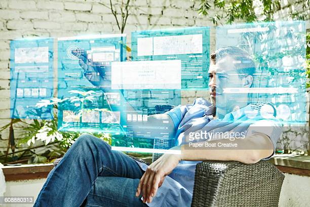 Man browsing hologram projection of work from home