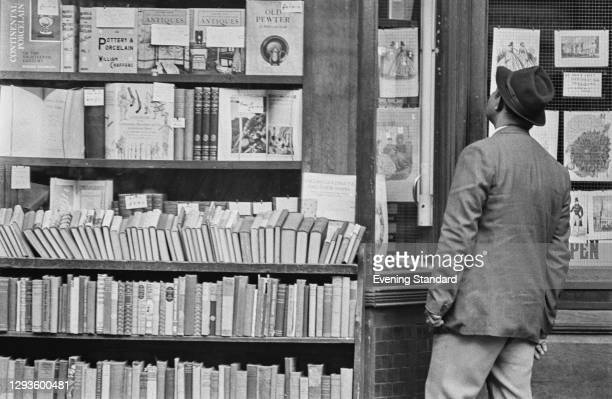 Man browsing in a second-hand bookshop window, UK, August 1967.