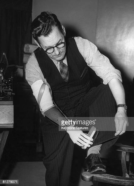 A man brushes his trousers turnups with an artificial hand July 1948