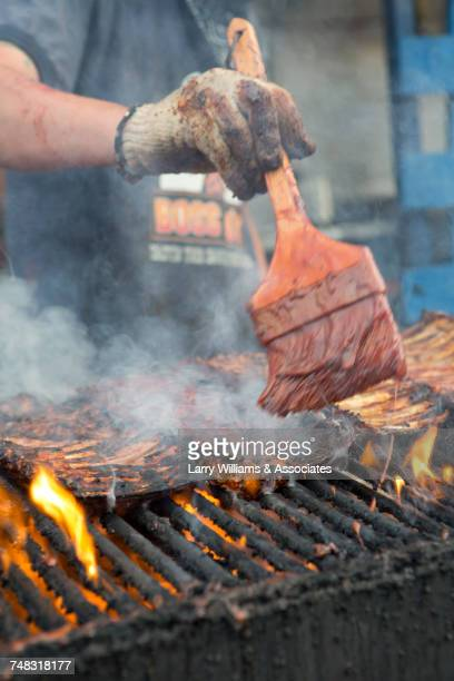 man brushing barbecue sauce on ribs cooking on grille - barbeque sauce stock photos and pictures