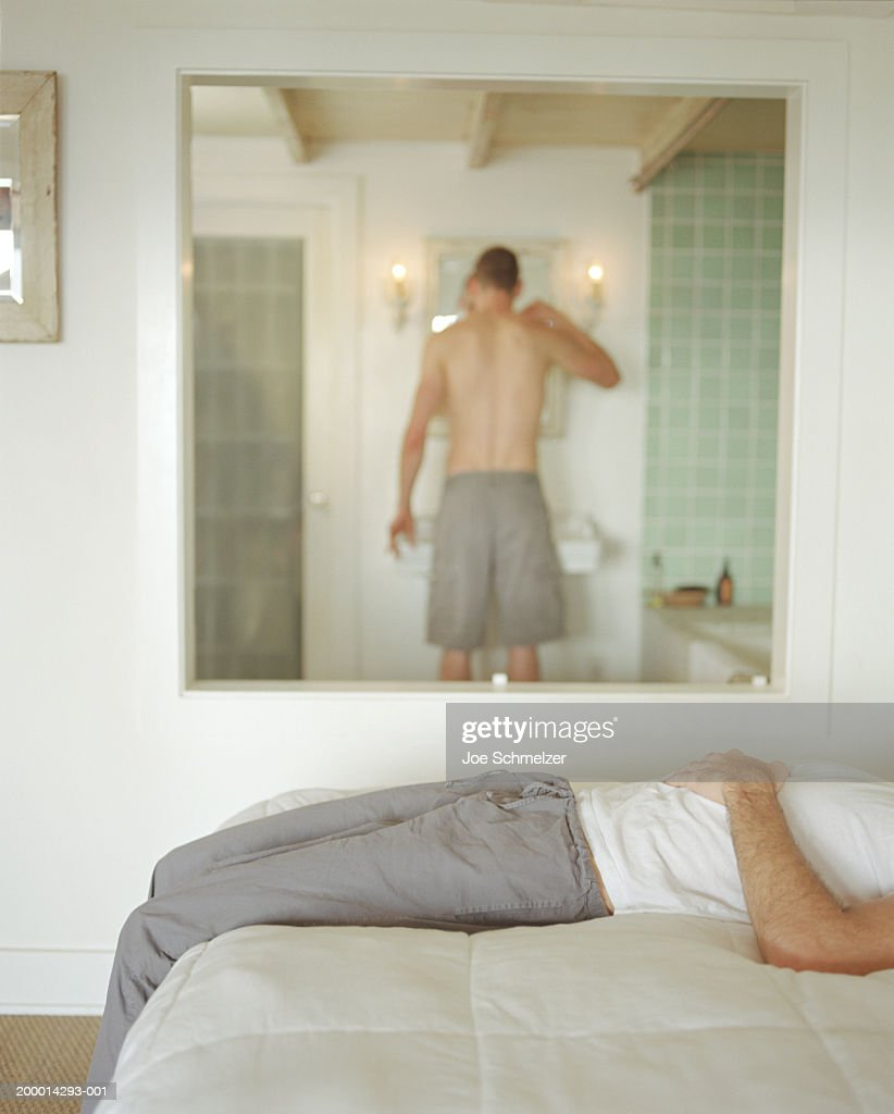 Man brushing his teeth, man lying in bed in foreground : Stock Photo