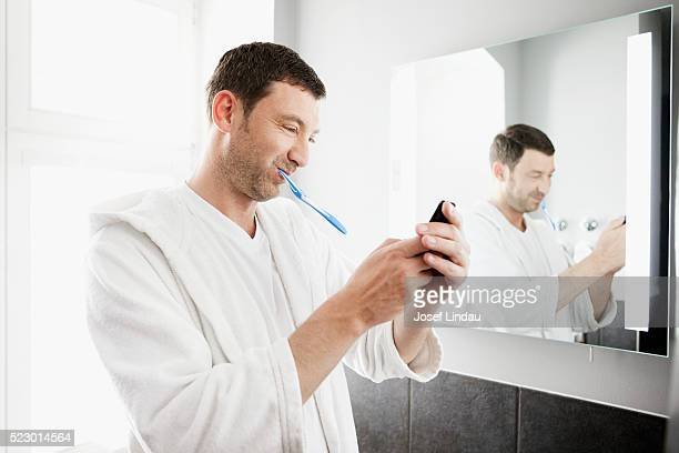 Man brushing teeth and text messaging