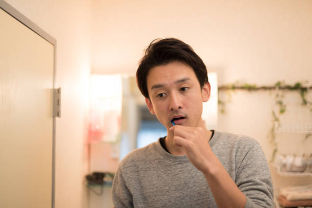 man brushing tooth in washing room - brush teeth stock pictures, royalty-free photos & images