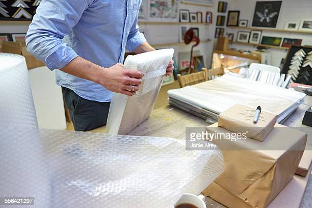 Man bubble wrapping picture frame on table in picture framers workshop