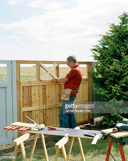Man building a fence in a garden Skane Sweden.
