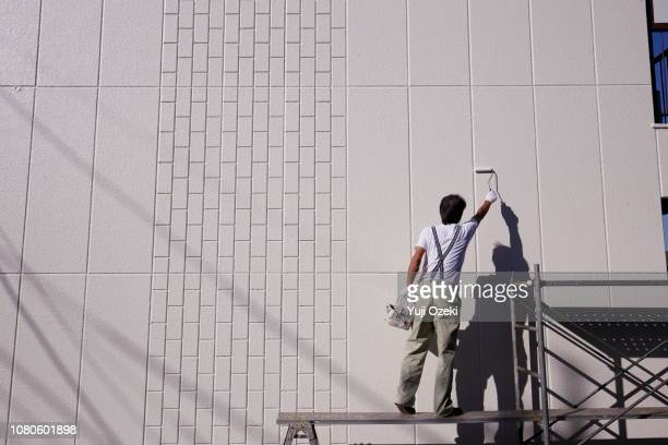 man building a foothold and painting a high wall - maler stock-fotos und bilder