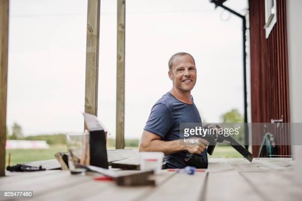 uomo che costruisce un patio fuori dalla sua casa di campagna - solo un uomo di età media foto e immagini stock