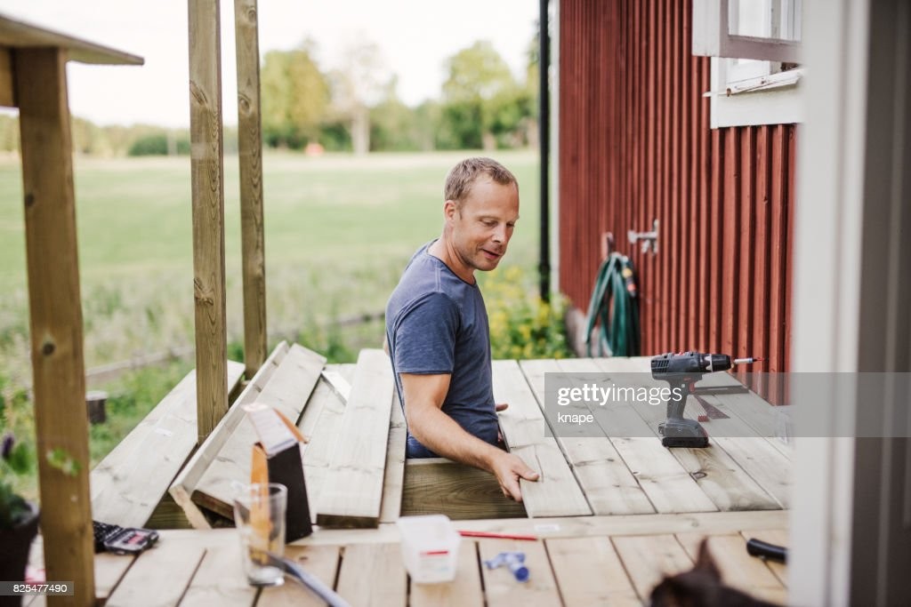 Man building a patio outside his country side house : Stock Photo