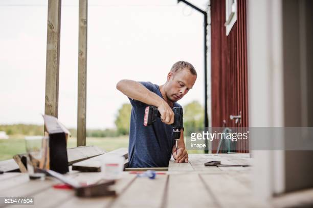 man building a patio outside his country side house - deck stock pictures, royalty-free photos & images