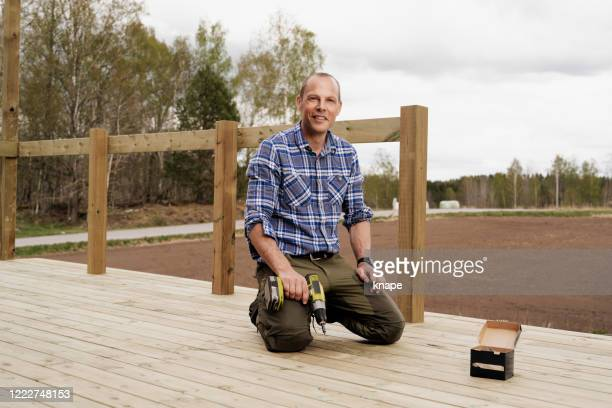 man building a wooden patio deck outdoors in his garden - decking stock pictures, royalty-free photos & images