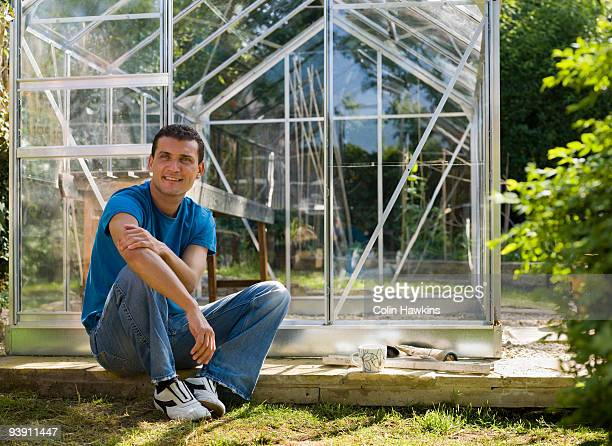 man building greenhouse in garden - colin hawkins stock pictures, royalty-free photos & images