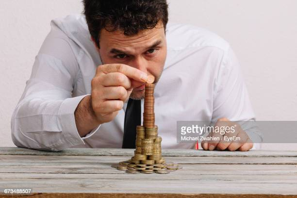 Man Building Stack Of Coins On Table Against White Background