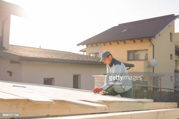 Man building the roof of wooden chalet