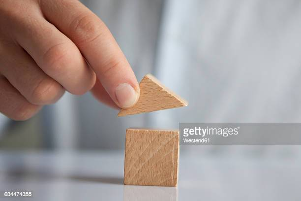 Man building up house with building blocks, close-up