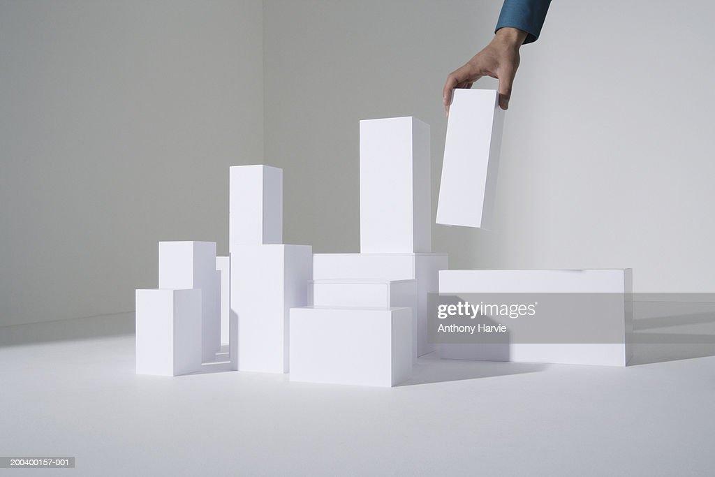 Man building white blocks, close-up : Stock Photo