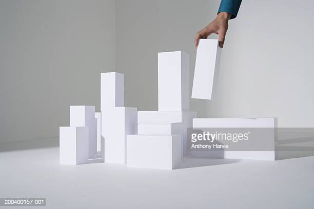 man building white blocks, close-up - europese etniciteit stockfoto's en -beelden