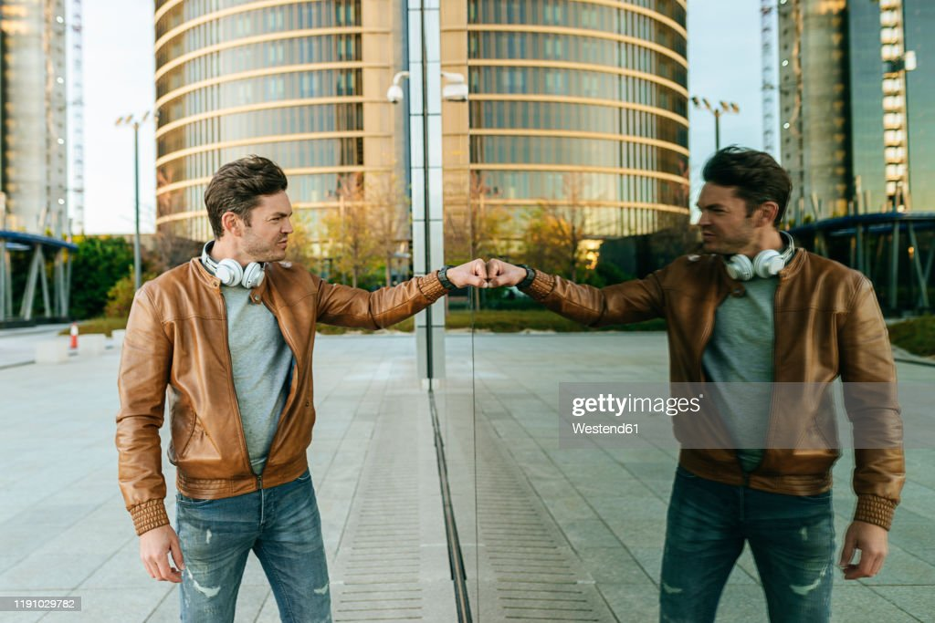 Man bumping fist with his reflection in glass pane of an urban building, Madrid, Spain : Stock Photo