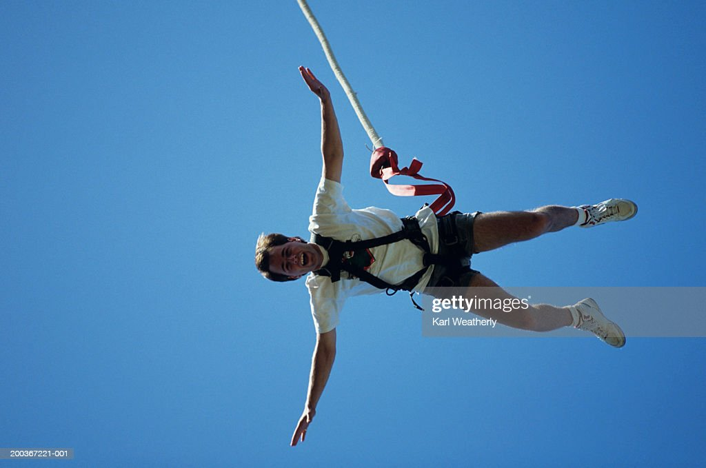 Man bungee jumping, seen against blue sky, view from below : Stock Photo