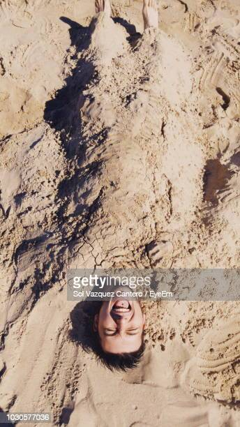 man buried in sand at beach - buried stock pictures, royalty-free photos & images