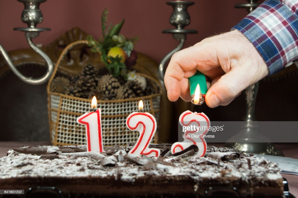 man burning candles with a lighter : Stock Photo