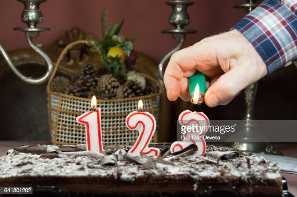 man burning candles with a lighter