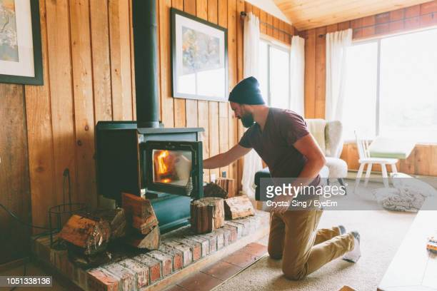 man burning firewood at home - firewood stock pictures, royalty-free photos & images