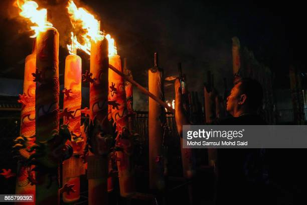 A man burns a joss stick as he performs a prayer during The Nine Emperor Gods Festival inside the temple on October 24 2017 in Kuala Lumpur Malaysia...