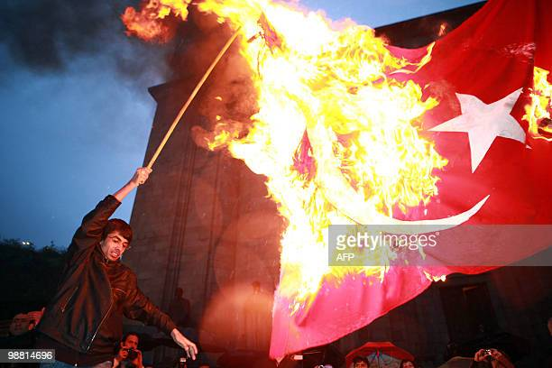 A man burns a Turkish flag while marching through the streets of Yerevan on April 23 2010 on the eve of the 95th anniversary of Ottomanera mass...
